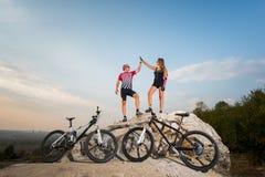 Пары велосипедиста стоя на утесе и давая максимум 5 Стоковое Изображение RF