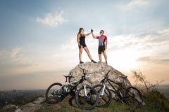 Пары велосипедиста стоя на утесе и давая максимум 5 Стоковые Изображения