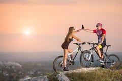 Пары велосипедиста с горными велосипедами на холме на заходе солнца Стоковое фото RF