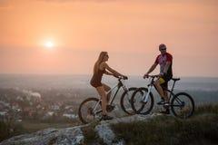 Пары велосипедиста с горными велосипедами на холме на заходе солнца Стоковое Изображение RF