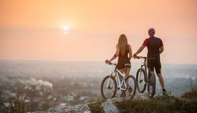 Пары велосипедиста с горными велосипедами на холме на заходе солнца Стоковые Фотографии RF