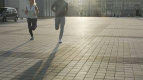 Пары взрослых друзей jogging в районе метрополитена, медленно причаливая камеры сток-видео