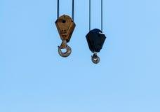 Пары висеть промышленные подъемы крана на бледном - голубое небо Стоковая Фотография
