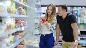 Пары влюбленн в покупки тележки в супермаркете видеоматериал
