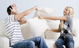 пары воюют иметь детенышей софы подушки Стоковое Изображение RF
