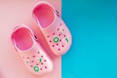 Пары вскользь удобных розовых ботинок лета для детей на розовой, голубой предпосылке, ботинках детей для пляжа, моря и Стоковое Изображение