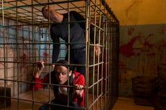 Пары вспугнутых жертв хеллоуина заключенных в турьму в lo клетки металла Стоковые Фото