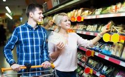 Пары выбирая сыр на магазине Стоковые Фотографии RF
