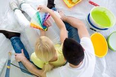 Пары выбирая цвета для красить новый дом стоковые фото
