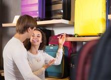 Пары выбирая чемодан перемещения в магазине haberdashery Стоковое Изображение