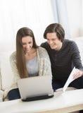 Пары высчитывая финансы на компьтер-книжке Стоковая Фотография