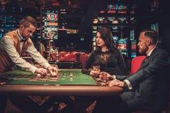 Пары высшего класса играя в азартные игры в казино стоковое фото