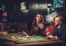 Пары высшего класса играя в азартные игры в казино стоковое изображение
