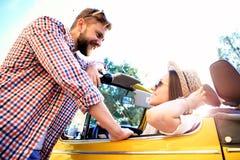 Пары в автомобиле с откидным верхом Красивые молодые пары наслаждаясь поездкой в автомобиле с откидным верхом и смотря один друго Стоковое фото RF