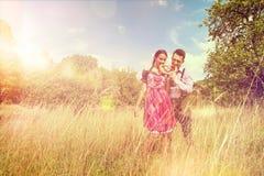 Пары в баварских одеждах едят prezel снаружи Стоковое фото RF