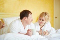 Пары в белых купальных халатах выпивая кофе совместно в кровати Стоковое Фото