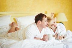 Пары в белых купальных халатах выпивая кофе совместно в кровати Стоковое фото RF