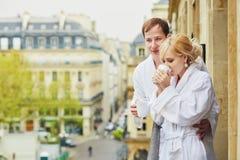 Пары в белых купальных халатах выпивая кофе совместно на балконе Стоковое Фото