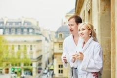 Пары в белых купальных халатах выпивая кофе совместно на балконе Стоковые Фото