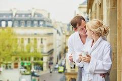 Пары в белых купальных халатах выпивая кофе совместно на балконе Стоковые Фотографии RF
