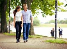 Пары в влюбленности гуляя в парке Стоковые Изображения