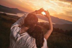 Пары в влюбленности делая сердце - сформируйте при руки, смотря заход солнца Стоковые Изображения RF