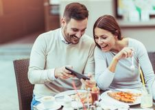 Пары в влюбленности имея потеху и есть пиццу в кафе Стоковые Изображения RF