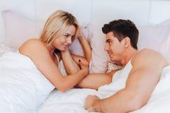 Пары в влюбленности лежа на кровати стоковые фото