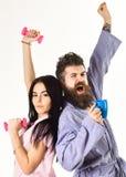 Пары в влюбленности в пижаме, купальном халате стоят спина к спине Концепция энергии утра Девушка с гантелью, человек с кофейной  Стоковые Изображения