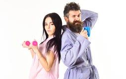 Пары в влюбленности в пижаме, купальном халате стоят спина к спине Концепция энергии утра Девушка с гантелью, человек с кофейной  Стоковое Изображение RF