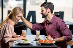 Пары в влюбленности имея обед в ресторане совместно Стоковая Фотография RF
