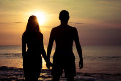 Пары в влюбленности подпирают светлый силуэт на море Стоковые Изображения RF