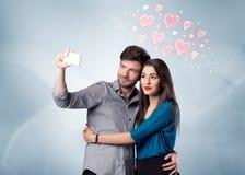 Пары в влюбленности принимая selfie с красным сердцем Стоковая Фотография