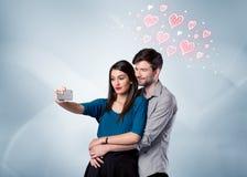 Пары в влюбленности принимая selfie с красным сердцем Стоковое фото RF