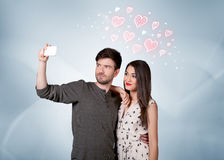Пары в влюбленности принимая selfie с красным сердцем Стоковое Изображение