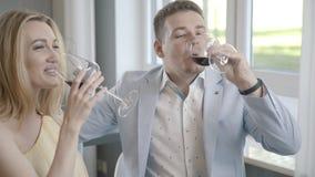 Пары в влюбленности сидят следующий один другого и выпивают вино, clinking для влюбленности видеоматериал
