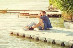 Пары в влюбленности сидя на пристани, объятии Стоковое Фото