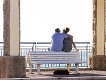 Пары в влюбленности сидя на стенде Стоковая Фотография