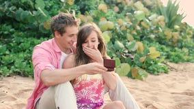 Пары в влюбленности, укомплектовывают личным составом удивительно его партнера с обручальным кольцом на пляже