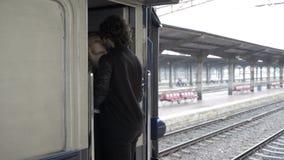 Пары в влюбленности целуя и обнимая до свидания в железнодорожном вокзале перед уходить на дождливый день видеоматериал