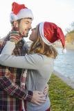 Пары в влюбленности outdoors с шляпами рождества Стоковые Фотографии RF