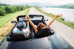 Пары в езде влюбленности в автомобиле cabriolet стоковое изображение