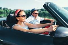 Пары в езде любов в автомобиле cabriolet стоковое фото