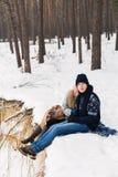 Пары в лесе зимы сидя на одеяле на пропасти Стоковое Фото