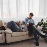 Пары в живущей комнате преследованной со смартфонами стоковая фотография