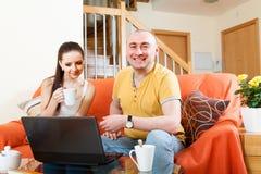 Пары в живущей комнате работая на компьтер-книжке Стоковая Фотография