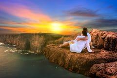 Пары в заходе солнца объятия наблюдая Стоковые Изображения RF
