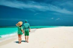 Пары в зеленом цвете на пляже на Мальдивах Стоковые Изображения