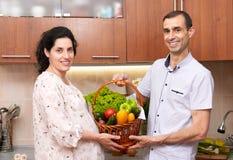Пары в интерьере кухни с корзиной свежих фруктов и овощей, здоровой концепции еды, беременной женщины и человека Стоковое Изображение