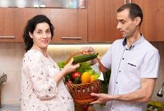 Пары в интерьере кухни с корзиной свежих фруктов и овощей, здоровой концепции еды, беременной женщины и человека Стоковые Фотографии RF